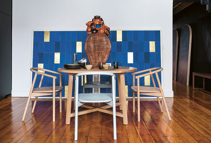 The indoor dining area features a round Harvest table and Hardwood chairs, all by James Mudge. The two artworks against the wall are by Morné Visagie and the ceramics are by Imiso.