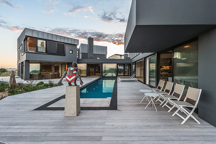 The splash pool in the main entrance gallery is aligned with the outdoor pool. The guest zone is to the left and the main living block to the right. The outdoor loungers and chairs are from Mobelli Furniture + Living, and the wicker set, far left, is from Plaisir du Jardin.