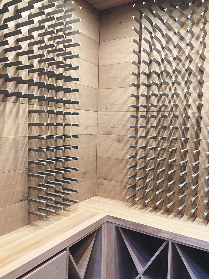 The wine room continues the wood theme with a timber peg display system by Display Wines.