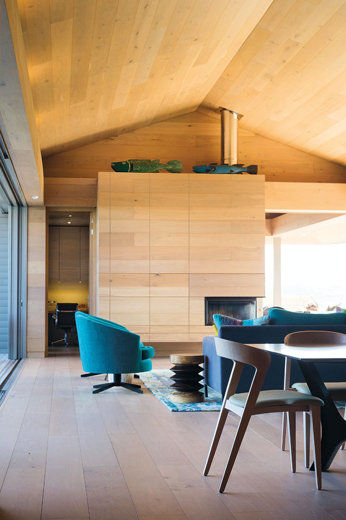 The timber-clad main living space opens to the sea on one side and views of the Outeniqua Mountains on the other. Joanne Kuny Interiors was tasked with selecting furniture.