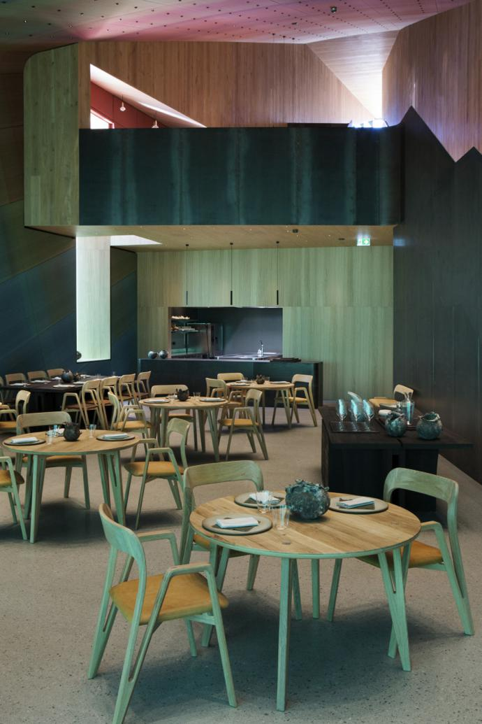 The main dining room features terrazzo flooring and blue and green acoustic panels inspired by the hues of the sea. The champagne bar above has warmer pink and orange tones to evoke shells and sand higher on the shore. Image credit: Inger Marie Grini/Bo Bedre Norge