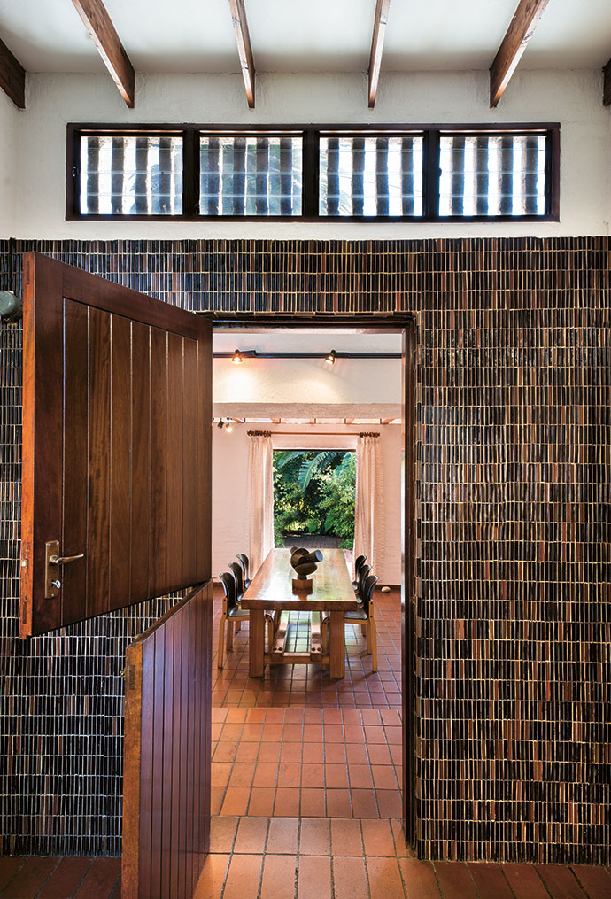The walls of the kitchen, with their original mosaic still immaculate, frame a view through the dining room to the garden. The table was designed for the space by the architect, Ian McLennan.