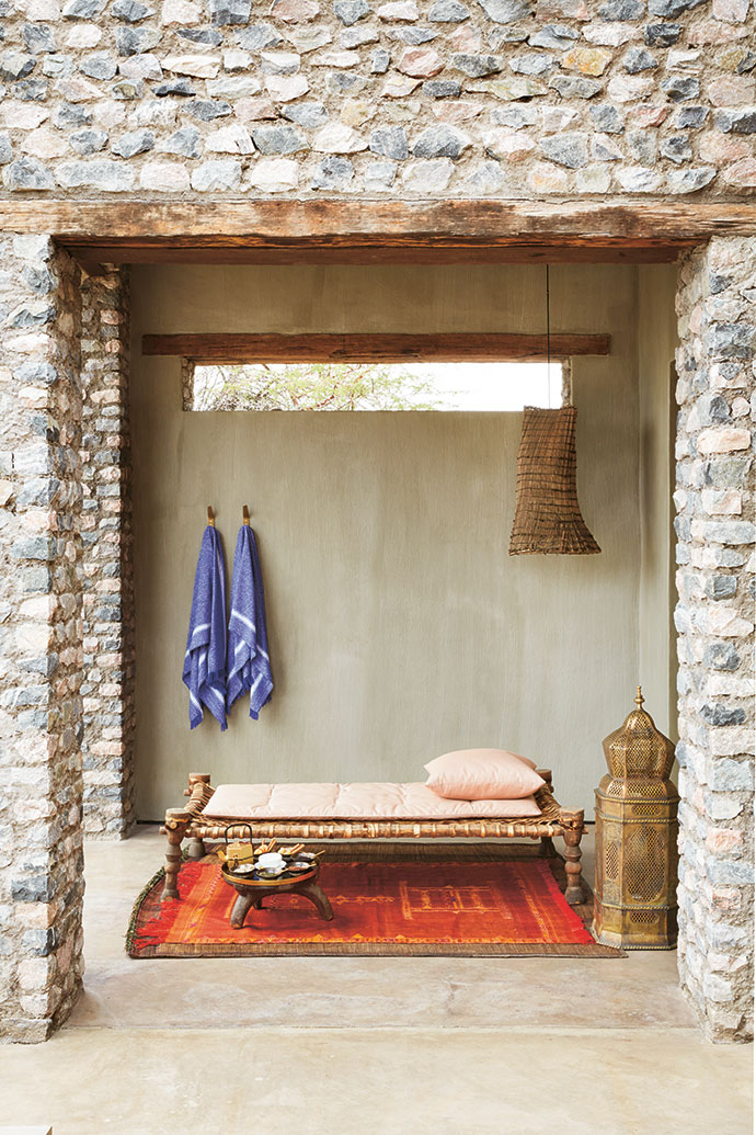 An African daybed sits on a Moroccan leather-and-reed mat and a Moroccan silk throw in the guest casita.