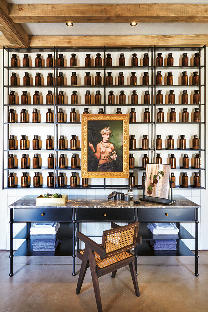A piece by Andrew Putter in a gilded frame hangs in front of the library of blended bath salts in brown reagent bottles, above a metal-and-marble vanity.