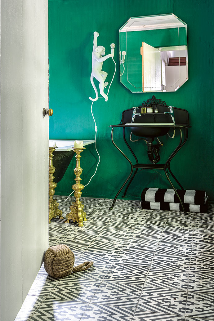In the green master bathroom, the floor tiles are from Moroccan Warehouse and the Seletti Hanging Monkey lamp from Generation.