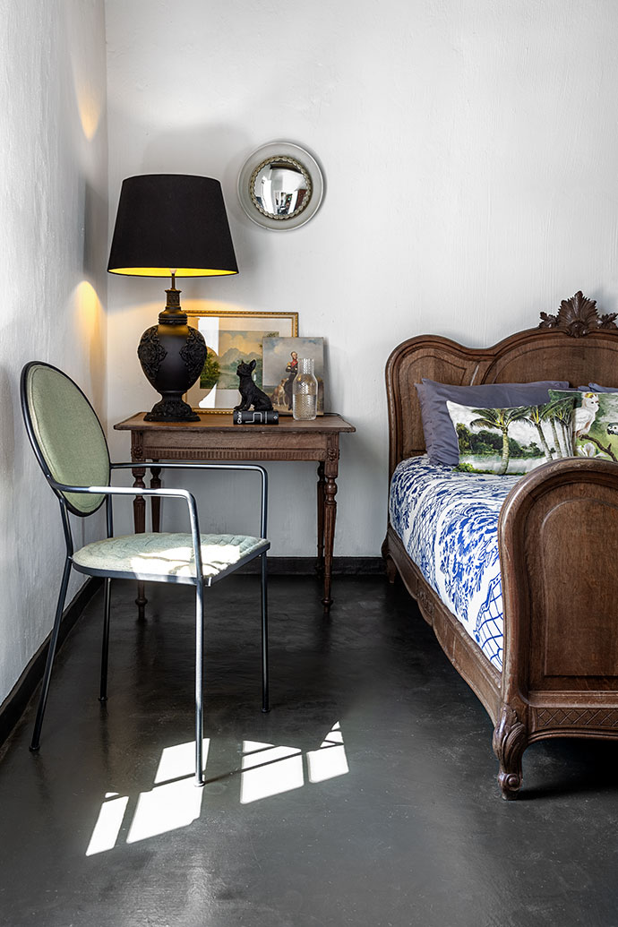 The guest bedroom is decorated with antique furniture and a Delft-print bedcover from Babylonstoren.