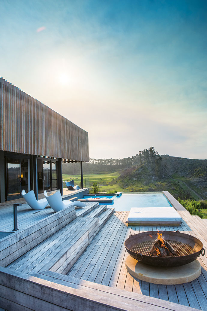 """The distinctive screen is made of vertical garapa hardwood blades. """"It gives the building a lightness and harmony with its surroundings,"""" says architect Guy Ailion. Paul and Viki bought the loungers at Nikki Beach on the island of Ibiza."""