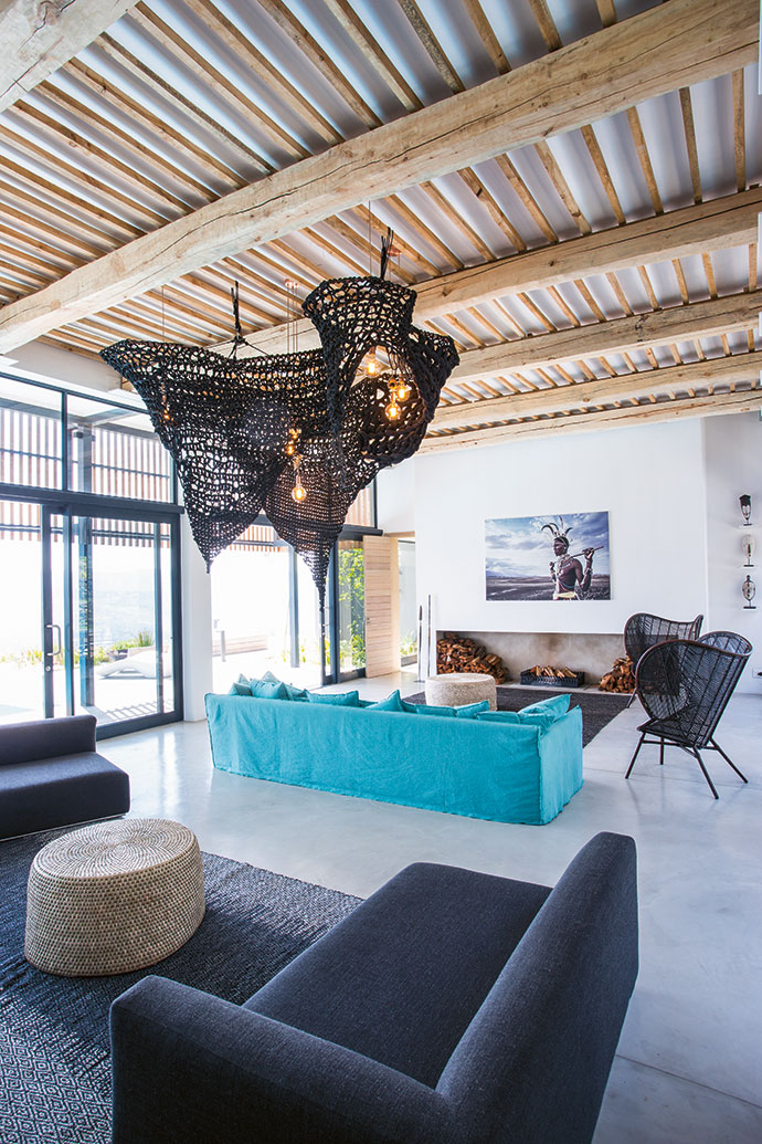"""Paul describes the aesthetic of the house as """"contemporary tribal"""", where modern Western design blends seamlessly with African tribal flourishes. Above the fireplace is a print of a David Ballam photograph, Rendille Moran VI, Lake Turkana, Kenya."""