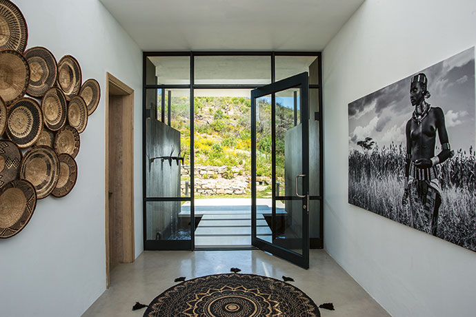 """""""Once inside, you are received in a gallery hall with a double-volume turret and a view through a courtyard, past the living room and out to the deck,"""" says architect Guy Ailion. """"This engages a visitor with the depth of the house and its sitting in the landscape."""" A collection of African baskets and a large print of a David Ballam photograph of a Hamer woman from the Omo Valley in Ethiopia adorn the walls."""