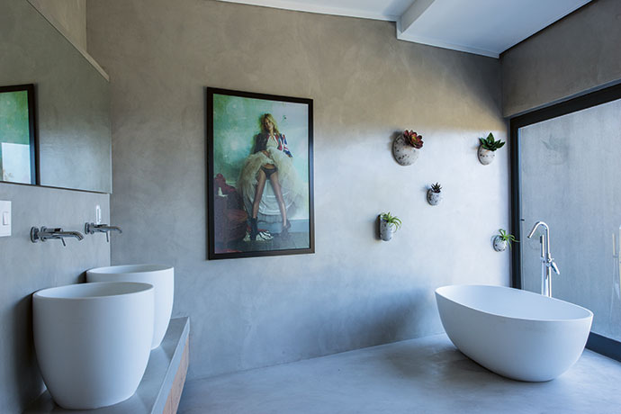 The bathroom is one of the edgier rooms in the house. Contrasting with the photograph of Kate Moss by Mario Testino is a collection of artfully displayed succulents. The DADO Toronto bath and Bleu basins are from PIPS in Plettenberg Bay.