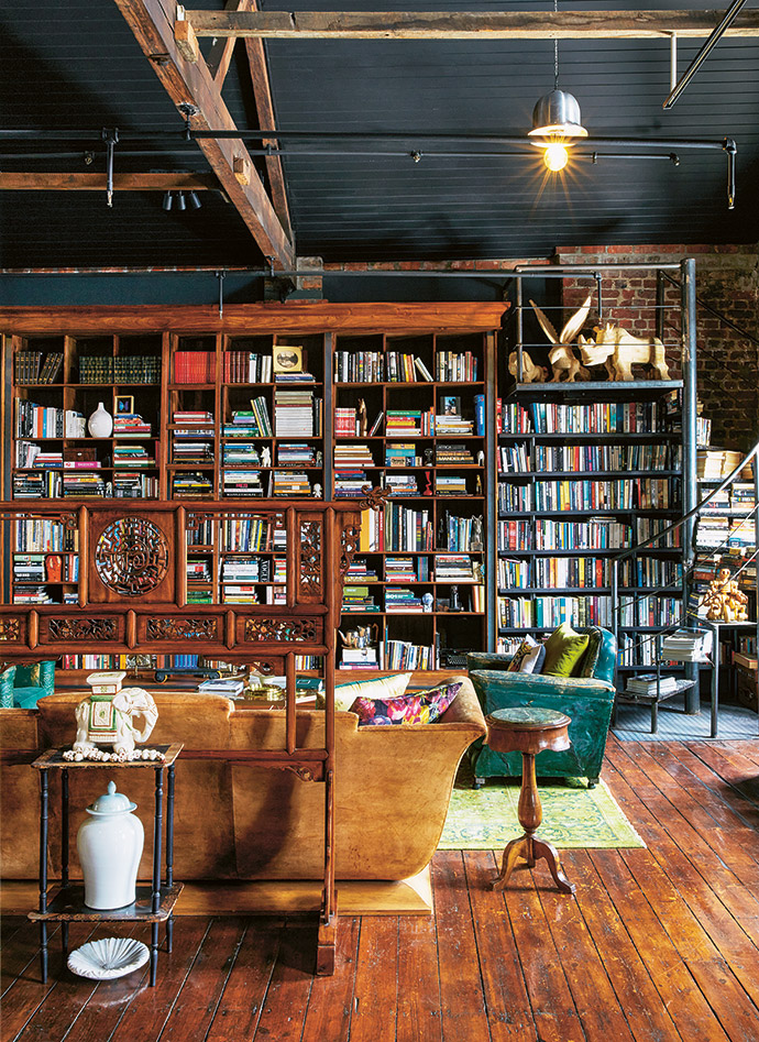 The bookshelves, built by Carlos La, are filled with well-thumbed books. The wooden sculptures above the shelves on the right are by a street artist, Michael, who carves his works under a tree by the side of the road.