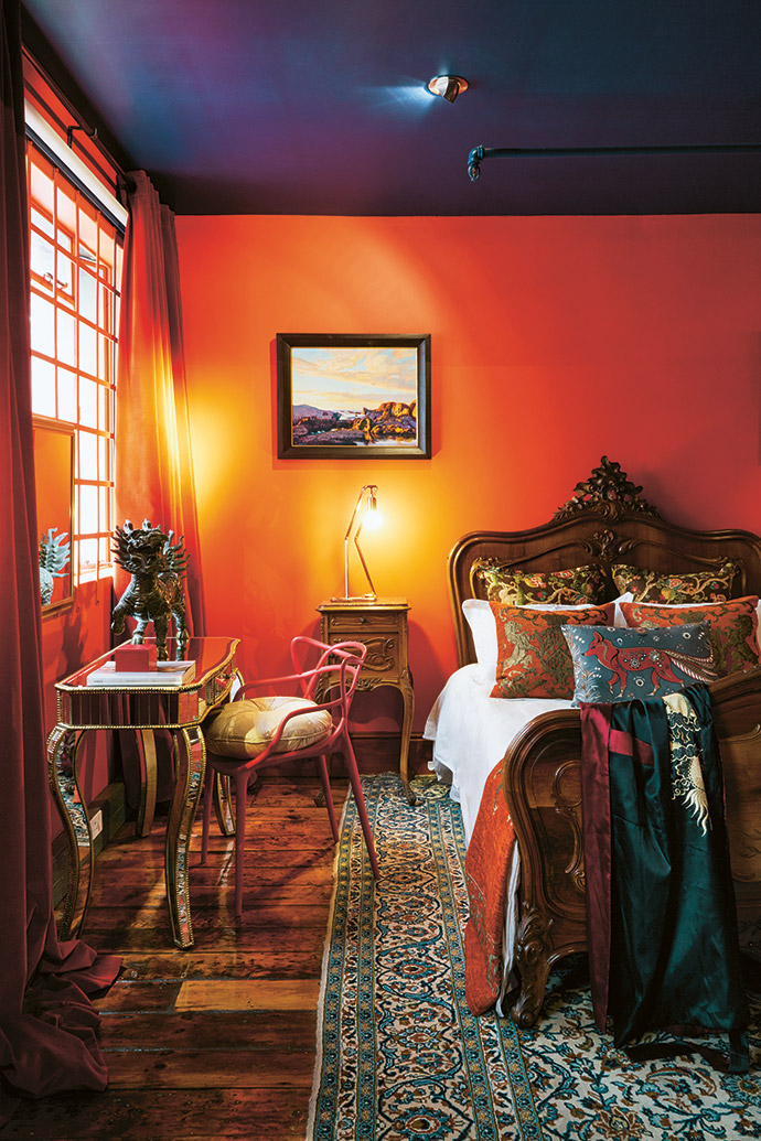 The guest bedroom features coral walls and velvet drapes, an antique French bed from Le Brocanteur, cushions and throws from The Hall Collection and a painting by Walter Meyer.