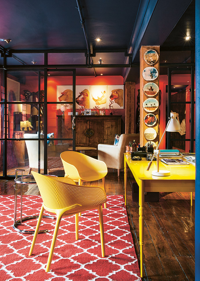 """An office features coral walls (Midas Setting Sun), a deep-blue ceiling (Duram Satin Touch Deep Well) and yellow accents. The glass-and-metal partitions are recycled warehouse fittings, and the chairs and side table are from Chair Crazy. The artwork in the background is by the homeowners' son, Henry """"Chomper""""."""
