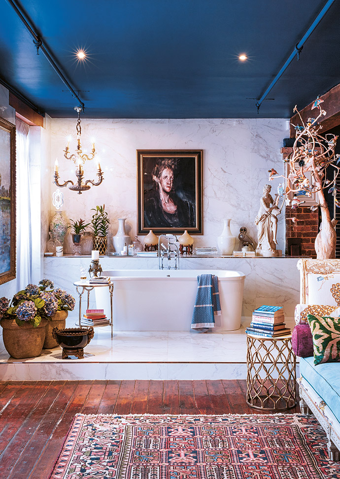 Next to the bath in the master bathroom is a handy ledge for cups of tea, magazines and books. The painting is by Italian artist Alessandro Papetti.