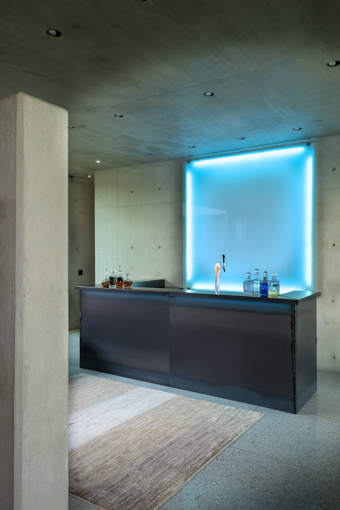 The bar is clad in mild steel, which was oiled and then fired to give it a distressed look. Behind the bar, a sheet of white glass backlit with a blue light emits a cool glow.