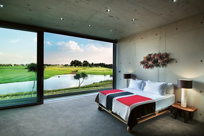Spectacular views onto the 10th and 18th holes can be had from all the bedrooms. In this bedroom, a wooden Weylandts bed base is teamed with a bright blanket and metal wall art, also from Weylandts.