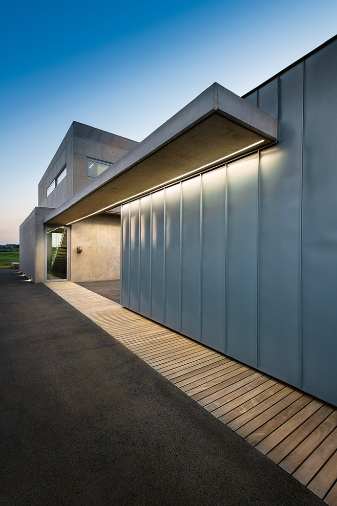 North light floods the passage through sliding windows and frosted-glass doors to each of the bedrooms. All plumbing and wiring are concealed behind steel panels.