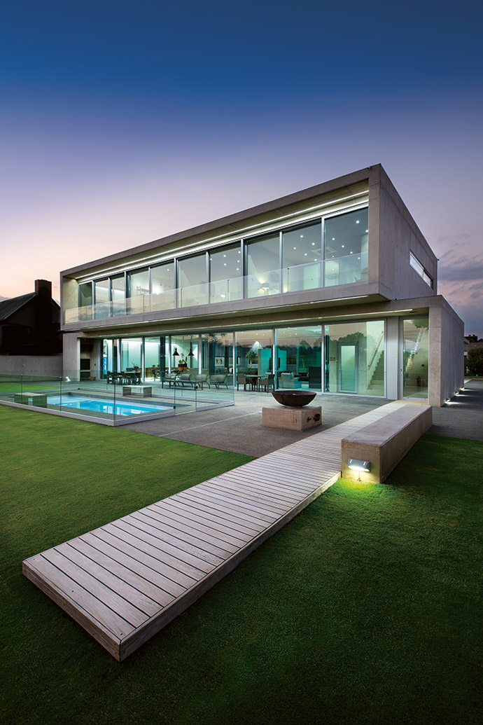 The south face of the house clearly demonstrates the two stacked cubes, with a 3 m-deep cantilever creating a sizeable patio that the Smiths use all summer long. The three bedrooms and the living areas all look out onto the garden and golf course.