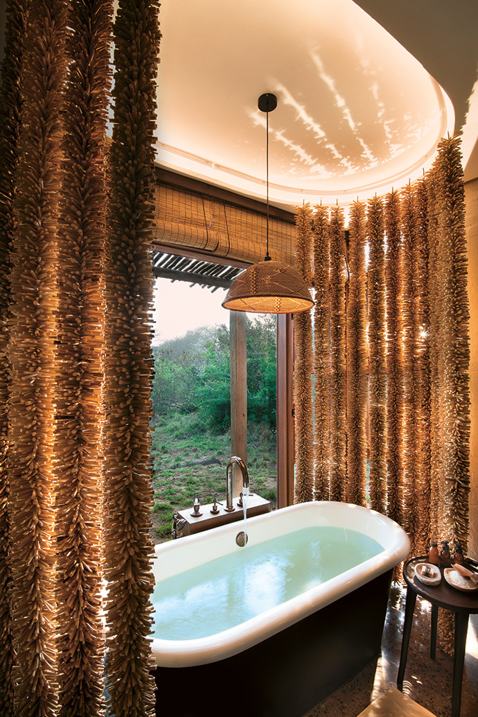 Hand-strung reed curtains in the bathroom provide privacy and create a sense of authenticity. Simple bamboo blinds and a custom-made woven pendant lampshade continue the rustic theme.
