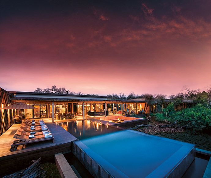 Sunken seating around the outdoor firepit affords guests the best vantage point to experience the fall of twilight in the bush. On the deck behind the sunloungers, which are from Core Furniture, herringbone sleeper cladding adds interest, especially at dusk when the downlighters are on.