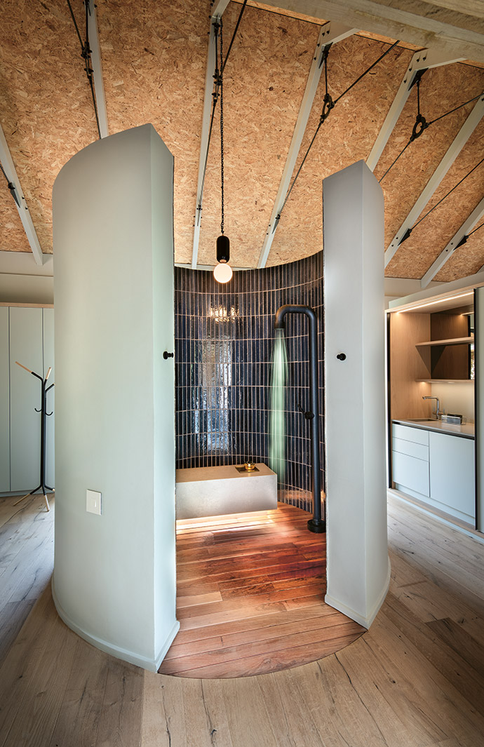 In the beautiful shower space between the bedroom and dressing room, the shower is by Linea Brigio and the light is from Floating Design. The Easy Coat coatstand in the background is by Dokter and Misses. The wooden flooring throughout the house is by Zuberi Flooring.