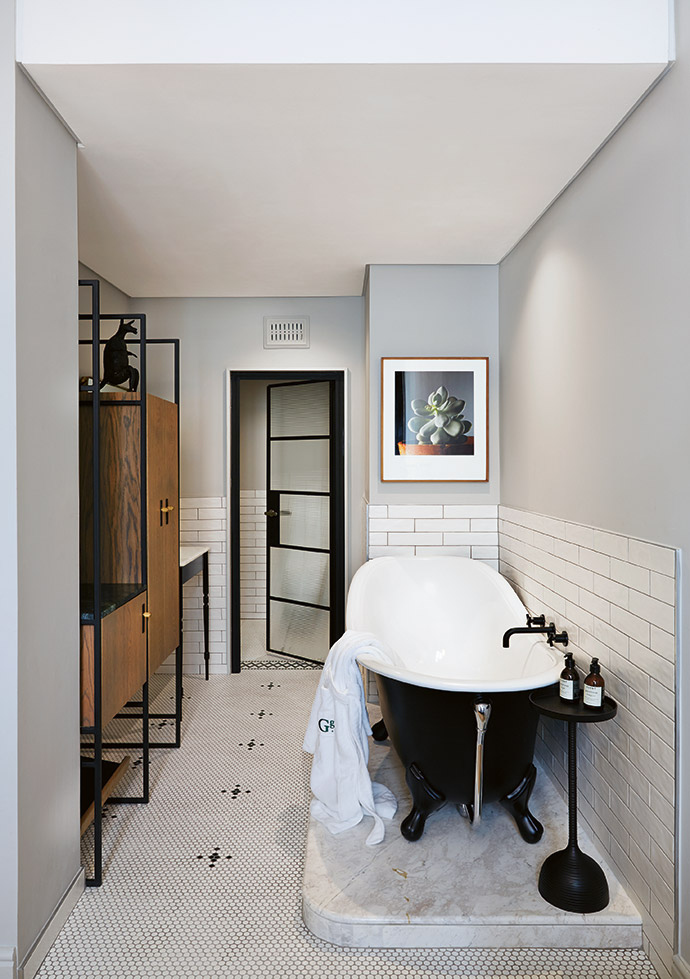 In this bathroom in a two-bedroom suite, the basin unit is by Gregor Jenkin and the cupboards are custom-made. The artwork is from Jac de Villiers' Vetplant series.