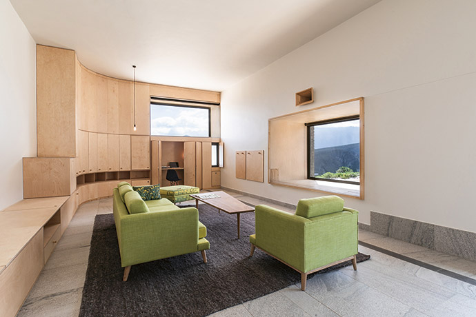 Three windows of different sizes and orientations were used in this space: one framing a view up the mountain and over the dam, one for ventilation, and one allowing the sun to penetrate the space during winter. The fireplace and study can be hidden from view when not in use. Wilna Hendriks from Ghost Fountain Design in Hermanus sourced the sofa and armchair from Klooftique and the ottoman from Casamento. The coffee table is designed by Ghost Fountain.
