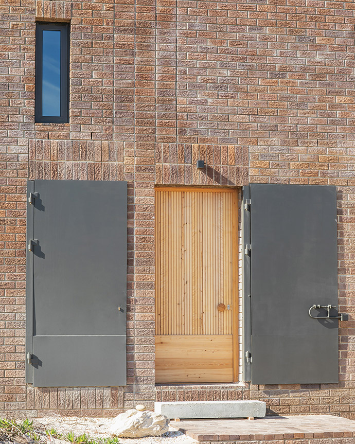 A set of steel doors conceals and protects the wooden front door and mechanical-room equipment from the elements and potential veld fires.